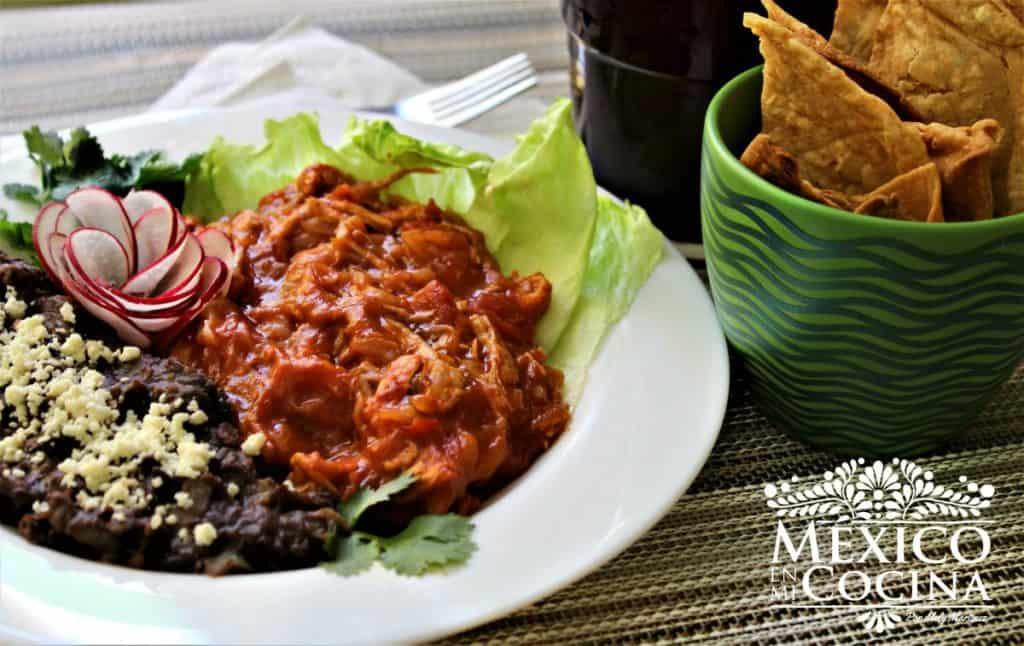 Plato de frijoles negros con carne polaca y tostadas.