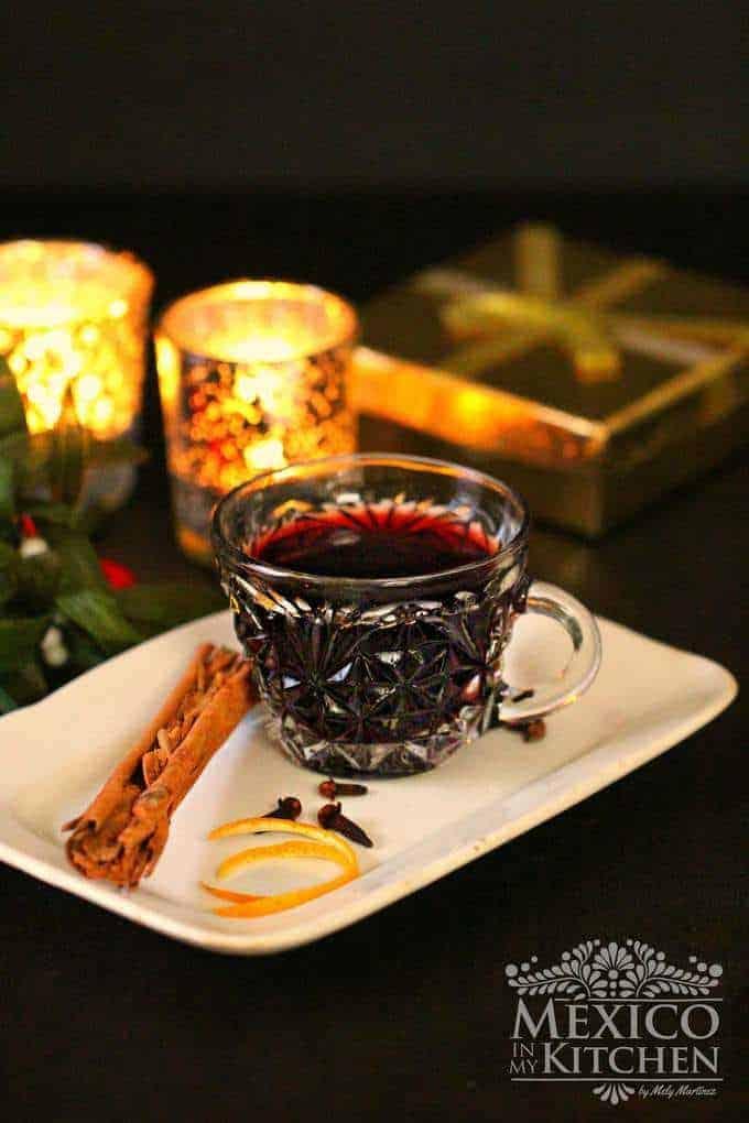 Vaso con vino caliente en un plato blanco, canela, clavos de olor y cáscara de naranja.